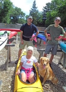 Woman sitting in a Kayak with dog by her side fluid fun kayak and canoe