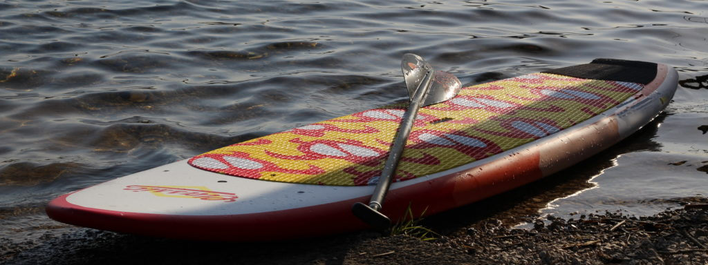 Paddleboard and Paddle on edge of water
