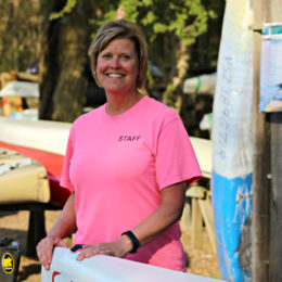 Manager Michele Clark standing near kayak fluid fun canoe and kayak